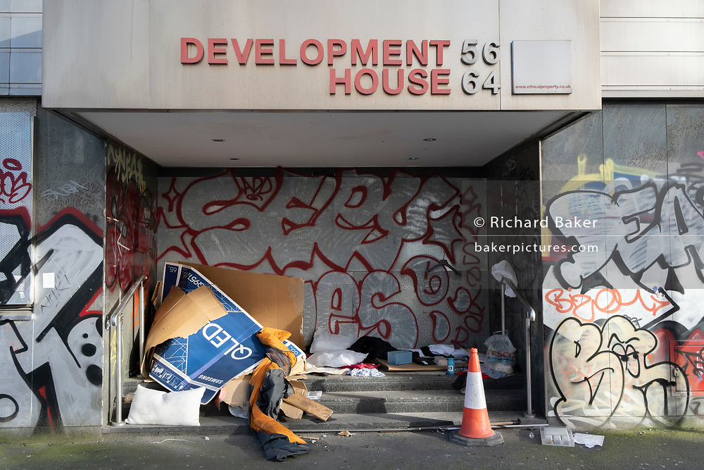 Cardboard boxes used for sheltering in and bedding to sleep under by homeless rough sleeper occupies the entrance of a former office property in Shoreditch, on 26th February 2021, in London, England.