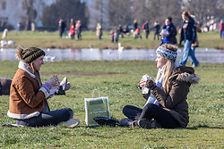 © Licensed to London News Pictures. 07/03/2021. London, UK. Friends in a bubble from Wimbledon enjoy a picnic together on Wimbledon Common in the sunshine this afternoon. From Monday, 8th March 2021 two friends will be allowed to socialise out side of their household for a coffee or picnic for the first time in months. England will begin Stage1 of the easing of lockdown tomorrow, with children returning to school, care homes allowing a visitor and friends being allowed to socialise out side of their household. However, pubs, shops and restaurants will still remain closed. Photo credit: Alex Lentati/LNP