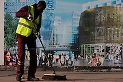 A utopian view of a London street sweeper brushing the street in front of a hoarding showing aspiration and consumerism of nearby Westfield City shopping complex, Stratford. Situated on the fringe of the 2012 Olympic park, Westfield hosted its first day to thousands of shoppers eager to see Europe's largest urban shopping centre. The £1.45bn complex houses more than 300 shops, 70 restaurants, a 14-screen cinema, three hotels, a bowling alley and the UK's largest casino. It will provide the main access to the Olympic park for the 2012 Games and a central 'street' will give 75% of Olympic visitors access to the main stadium so retail space and so far 95% of the centre has been let. It is claimed that up to 8,500 permanent jobs will be created by the retail sector.