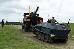 Magda the Sd.Kfz 251AufC Halftrack with wheel missing hooked up to Dooleys Dragster is towed from the Yorkshire Wartime Experience Arena at Hunsworth Lane Hunsworth West Yorkshire where  the where the recent AA Commercial she appeared in was filmed.<br /> <br /> 05 July 2015<br />  Image © Paul David Drabble <br />  www.pauldaviddrabble.co.uk