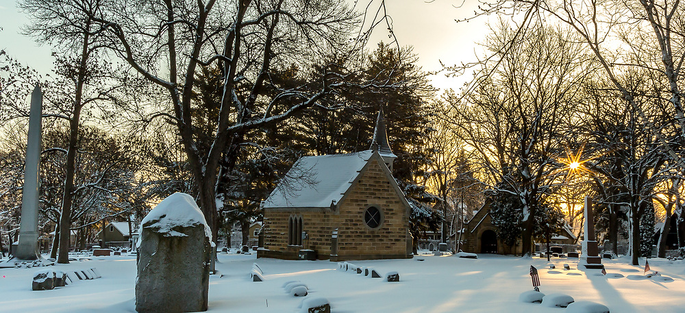 Early morning sun gives glorious light to American flags on snow covered graves of veterans in Forest Hill Cemetery near Catlin Chapel. Photo taken April 19, 2018, morning after a late spring snowfall.