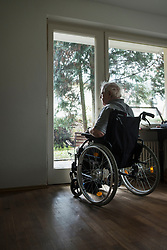 Senior man in wheelchair looking out through window, Altoetting, Bavaria, Germany, Europe
