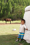 young boy leaning on the ger, Mongolia