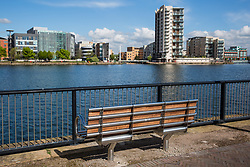 Cardiff, UK. 2nd May, 2017. A bench positioned opposite modern apartment blocks beside Roath Basin in Cardiff Docks.