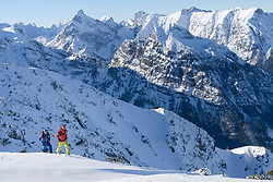 Skiers climbing on snow against mountain range
