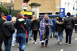 A vendor sells commemorative scarfs of the match outside the grounds of the stadium before the match begins