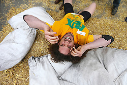 © Licensed to London News Pictures. 17/04/2017. Gawthorpe UK. UK. Competitor JOEL HICKS breaks down at the finish line of the mens race of The World Coal Carrying Championships in the village of Gawthorpe in Yorkshire. Every year Men & women carry huge sacks of coal from the Royal Oak Pub in Ossett 1012 metres to the finish line at the Maypole Green in the village of Gawthorpe. Photo credit: Andrew McCaren/LNP