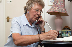 Elderly woman writing a note and talking on the telephone,