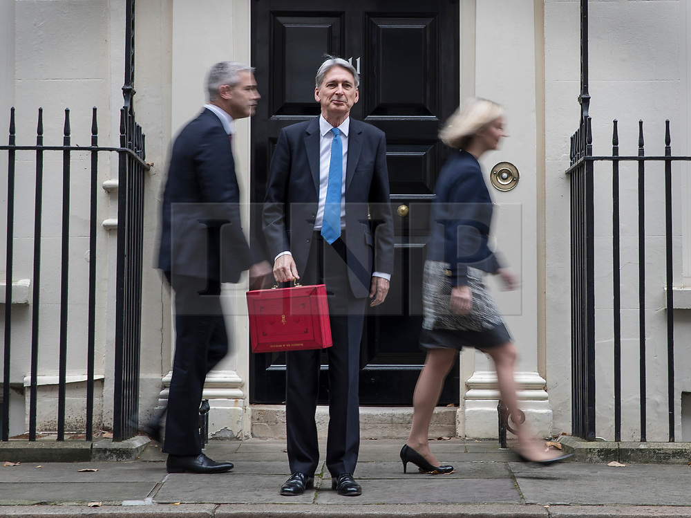 © Licensed to London News Pictures. 22/11/2017. London, UK. Chancellor of the Exchequer Philip Hammond holds his red ministerial box for photographers as Andrew Barclay, Economic Secretary to the Treasury and Liz Truss, Chief Secretary to the Treasury walk past Number 11 Downing Street on budget day. Photo credit: Peter Macdiarmid/LNP