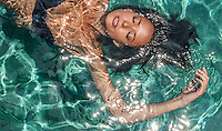 A floating woman rejuvenates herself in a tropical pool. LIfestyle photography by Djuna Ivereigh.