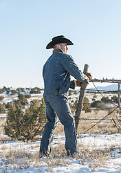cowboy working on a fence