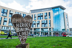 """© Licensed to London News Pictures; 08/12/2020; Bristol, UK. A sculpture saying """"The NHS Heroes saving lives for U"""" is seen at Southmead Hospital. Southmead Hospital is one of the hospital hubs for the first day of vaccination using the new vaccine against the Covid-19 coronavirus pandemic. The hospital, part of North Bristol NHS Trust, has been chosen as one of 50 'hospital hubs' across the nation and people aged 80 and over, as well as care home workers, will be first to receive the vaccine, along with NHS workers who are at higher risk. Bristol nurse Rob Healey whose death was reported yesterday, died after contracting coronavirus and worked in Southmead Hospital's emergency department and had tested positive for Covid-19. Photo credit: Simon Chapman/LNP."""