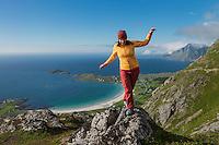 Female hiker walks across rocks on summit of Nubben, Ramberg, Flakstadøy, Lofoten Islands, Norway