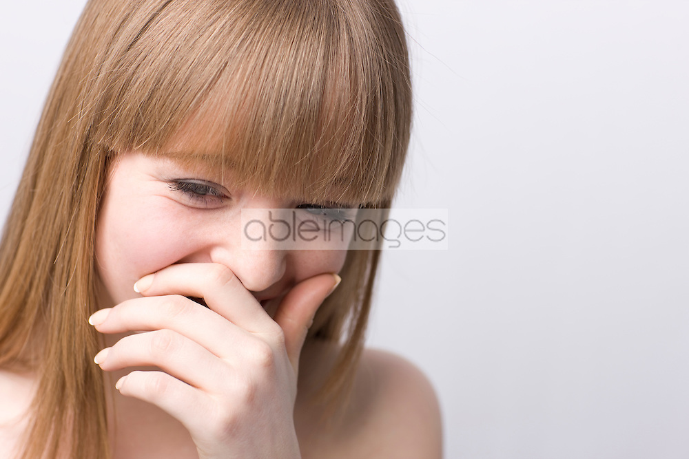 Young woman laughing with hand in front of mouth