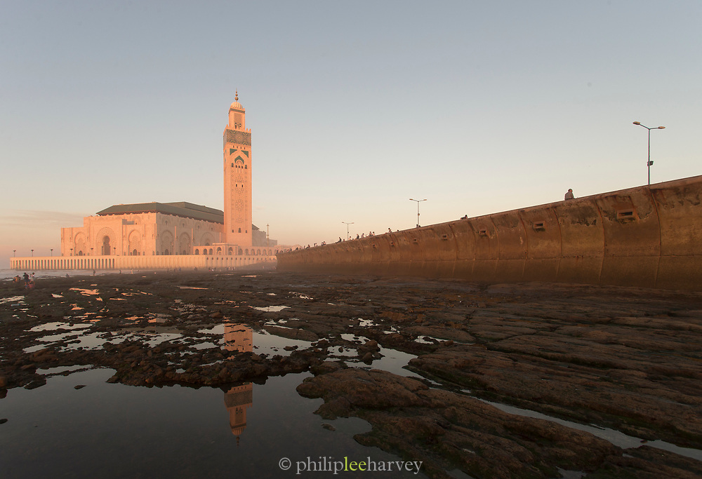 People walking along coast near Hassan II Mosque at foggy sunset. Casablanca, Morocco