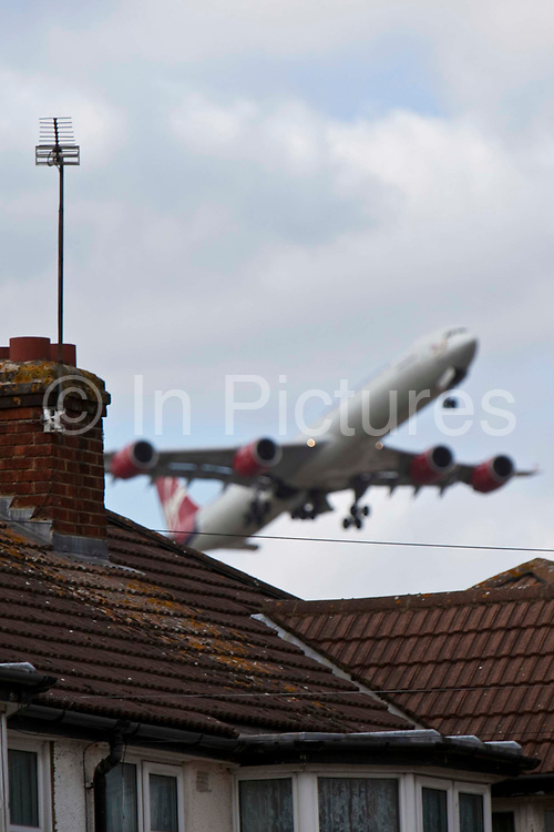 A Virgin Airbus A340 taking off from London Heathrow close by to local houses in Hatton.