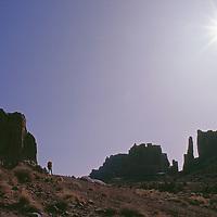 Hiker below sandstone towers in Arches National Park, Utah.