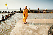 Apr. 3, 2010 - KHUN SAMUTCHINE, THAILAND: Abbot ATHIKARN SOMNUK ATIPANYO, walks along the sea wall that protects Wat Samutchine from the Gulf of Siam (in the background). Rising sea levels brought about by global climate change threaten the future of Khun Samutchine, a tiny fishing village about 90 minutes from Bangkok on the Gulf of Siam. The coastline advances inland here by about 20 metres (65 feet) per year causing families to move and threatening the viability of the village. The only structure in the village that hasn't moved, their Buddhist temple, is completely surrounded by water and more than 2 kilometers from the village. The temple and the village have asked the Thai government and several NGOs for help, but the only help so far is a narrow concrete causeway the government is building that will allow people to walk into the temple from a boat landing two miles away. The walk to the village from a closer boat landing is shorter, but over an unimproved mud flat that is nearly impassible in the rainy season.  PHOTO BY JACK KURTZ