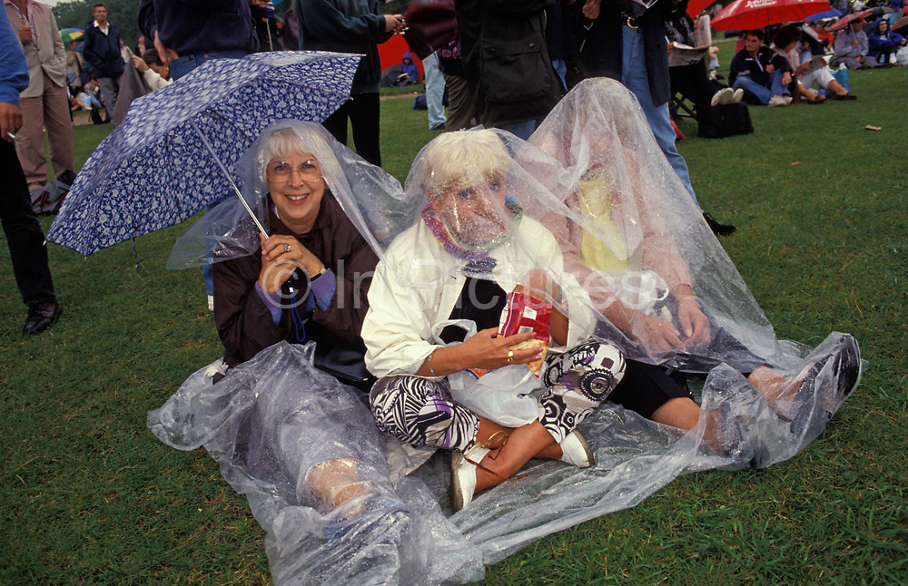 Rain-soaked opera fans sit on wet grass before the perfoamance by Italian operatic tenor Luciano Pavarotti during the free Party in the Park concert to celebrate his 30 years in opera, on 30th July 1991 in Londons Hyde Park, on 30th July 1991, in London, England. A crowd of 100,000 stood in the rain to watch Pavarotti perform 20 arias by Verdi, Puccini, Bizet and Wagner. VIPs the Princess of Wales, Prime Minister John Major and Michael Caine were soaked in heavy rain along with everyone else sitting on the grass cowering beneath tarpaulins. Pavarotti helped bring an otherwise high-brow artform to the ordinary Man after the BBC used his rendition of Nessun Dorma to theme their World Cup TV coverage.