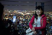 Junge Dame wird in abendlicher Stimmung auf der unteren Aussichtsplattform des N Seoul Towers in der koreanischen Haupstadt - umringt mit Wünschen versehenen Schlössern -fotografiert. Der N Seoul Tower ist ein der Öffentlichkeit zugänglicher Fernsehturm in der südkoreanischen Hauptstadt Seoul. Der 236,7 Meter hohe Turm steht auf 243 m ü. N.N. des Berges Namsan.<br /> <br /> Young woman gets  photographed during an evening mood at the lowest observation deck of the N Seoul Tower surrounded by lockers. N Seoul Tower is a communication tower located in Seoul, South Korea. Built in 1969, and opened to the public in 1980, the tower measures 236.7 m (777 ft) in height (from the base) and tops out at 479.7 m (1,574 ft) above sea level.