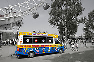 Day Tripper - London South Bank is a selective colour street photography series by photographer Paul Williams  of tourists and an ice cream van by the London Eye South Bank London taken in 2008 .