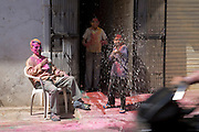 A boy squirts a water pistol at a motorcyclist as it passes his front door during the festival of Holi, in Udaipur, Rajasthan, India