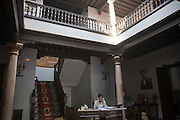 Woman sitting at desk in historic courtyard of building in the old city of Ronda, Spain