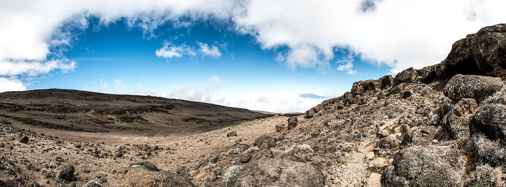 A panorama of the rocky, rugged apline desert on Mt Kilimanjaro Lemosho Route. These shots were taken on the trail between Moir Hut Camp and Lava Tower at approximately 14,500 feet. In the far distance is the summit of Mt Meru peaking up through the clouds.