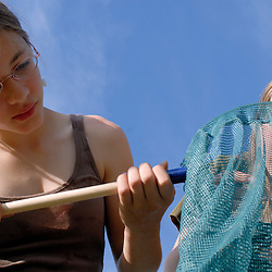 Amber Rabie, 12, and her sister Meladeh, 16, examine a bug caught in Amber's net...Photo by Susana Raab..