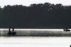03 June 2005:   a pair of small boats carrying men fishing are silhouetted against the stark contrasting background of a late afternoon sky and the shadows of the shoreline in late spring.