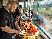 Anthony Bonilla, owner Gary D'Angelo's nephew, slicing a knish in the D'Angelos food trailer on Woodhaven Boulevard near St. John's Cemetery in Queens. Their trailer is a customized race car trailer, with the interior, including a solid stainless steel grill, fitted out by 800BuyCart, which has been outfitting D'Angelos since 1989. In keeping with the generally Italian menu, the knishes can be stuffed with sausage, onions and peppers.