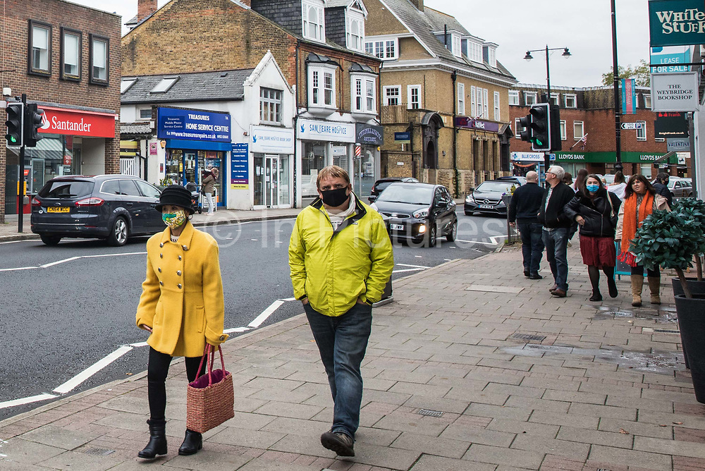 Shoppers wear face coverings to help prevent the spread of the coronavirus on 16 October 2020 in Weybridge, United Kingdom. The Government has announced that the Borough of Elmbridge, which contains the towns of Weybridge, Esher, Cobham, Walton-on-Thames and Molesey, will move into Tier 2 of the Government's new three-tier Local COVID Alert Level system for England with effect from 00.01 on Saturday 17th October, designating it an area of 'High' risk following a significant rise in the number of COVID-19 cases.