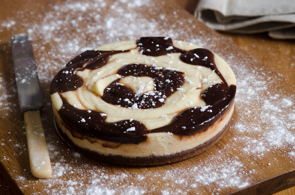 Delicious chocolate swirl cheesecake on a wooden board