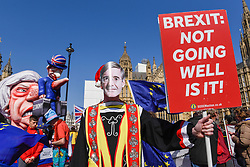 © Licensed to London News Pictures. 01/04/2019. LONDON, UK. An effigy of Theresa May, Prime Minister, is positioned with a Pro-Remain supporter wearing a Jacob Rees-Mogg face-mask during a protest outside the Houses of Parliament. MPs are debating eight motions related to Brexit with voting to begin later this evening.  Photo credit: Stephen Chung/LNP