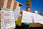 """07 FEBRUARY 2011 - PHOENIX, AZ: GEORGINA GRIVALJA, from Tucson, AZ, stands in support of birthright citizenship in front of the Arizona Capitol with a chain of hand drawn babies that represent """"anchor babies"""" Monday, February 7. The Arizona State Legislature, led by the State Senate is debating the 14th Amendment, which would bar US citizenship for the children of undocumented immigrants born in the United States. The bill has broad support among Republicans, who are the majority party, in the state legislature but not among Democrats. The law is also very unpopular in the state's Latino and immigrant communities.       Photo by Jack Kurtz"""