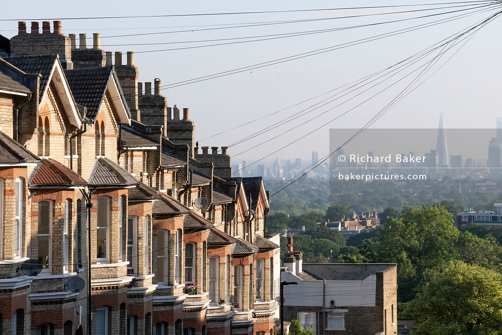 Terraced homes with an elevated viewpoint of the London skyline at Crystal Palace, on 16th June 2021, in London, England.