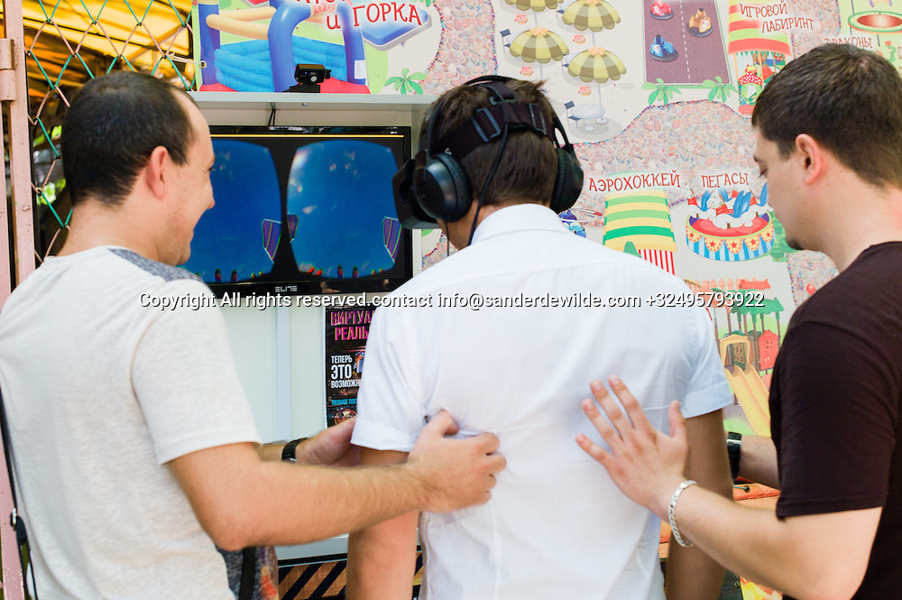 20150829  Moldova, Transnistria,Pridnestrovian Moldavian Republic (PMR) Tiraspol. In the amusement park within paboda park friends keep a guy from falling who is trying a 3D experience in the open air.