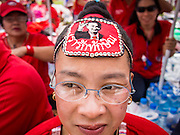 """19 NOVEMBER 2013 - BANGKOK, THAILAND: A Red Shirt protestor, wearing a Thaksin Shinawatra visor, cheers for speakers during a Red Shirt rally in Bangkok. As many as 30,000 """"Red Shirts"""" are expected in Bangkok this week ahead of a Thai court ruling that could cause the collapse of the government of Yingluck Shinawatra, the Prime Minister. The Red Shirts are gathering in a suburban sports stadium before marching to the court. The Red Shirts are mostly farmers and rural Thais who support the Shinawatra government.     PHOTO BY JACK KURTZ"""