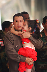 President Hugo Chavez holds a little girl that was called out from the crowd during the inaguration of a government subsidized market called Mercal.