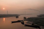 Bangladesh, waterway west of Dhaka at sunrise, with brick kiln factory smokestacks.
