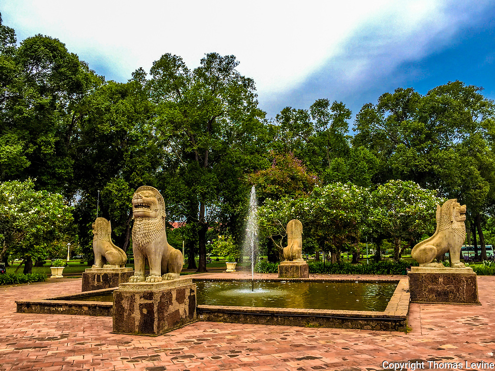 City park in Siem Reap with a pond with a fountain.  Surrounded by lion statutes.