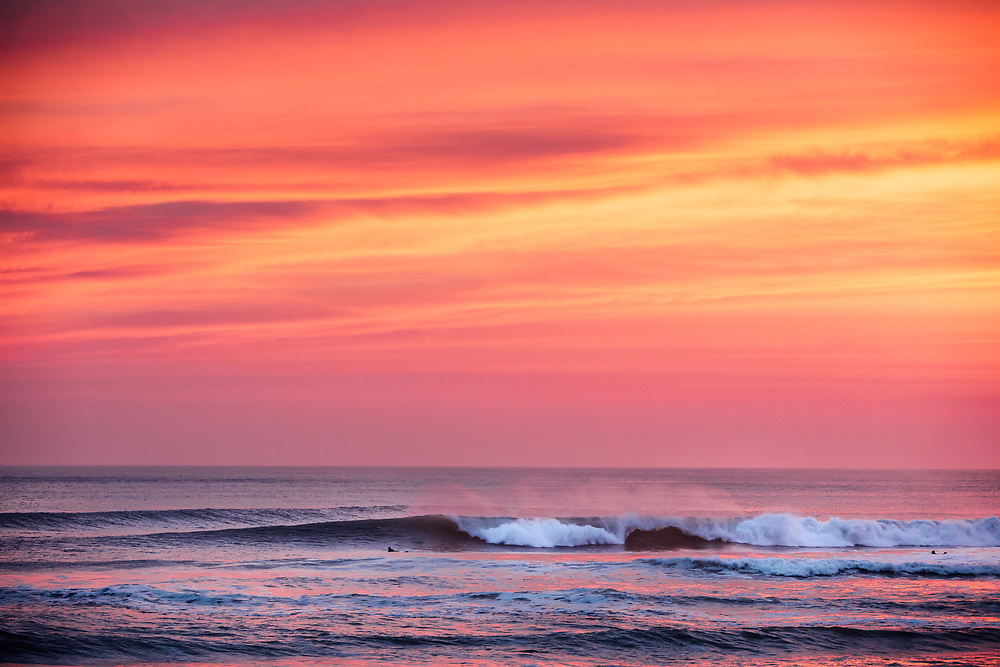 Orange and red sky reflecting in the surf after sunset. Man paddling out to catch the next wave in Jersey, Channel Islands