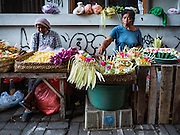 11 OCTOBER 2016 - UBUD, BALI, INDONESIA: Women sell flower garlands in the morning market in Ubud. The morning market in Ubud is for produce and meat and serves local people from about 4:30 AM until about 7:30 AM. As the morning progresses the local vendors pack up and leave and vendors selling tourist curios move in. By about 8:30 AM the market is mostly a tourist market selling curios to tourists. Ubud is Bali's art and cultural center.      PHOTO BY JACK KURTZ