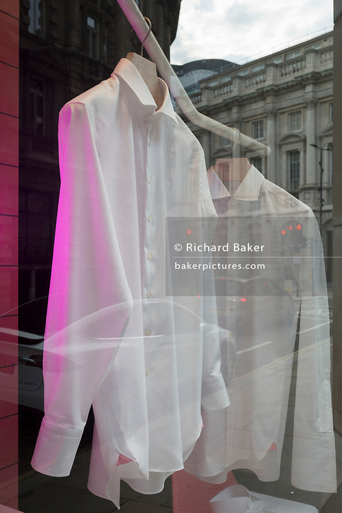 With the Coronavirus lockdown continuing into the Bank Holiday weekend, when Prime Minister Boris Johnson is due to tell the nation that only a gradual easing of regulations and social distancing rules are still to be in place, two high-quality shirts hang in the window of a menswear outfitters in a deserted City of London, the capital's financial district, on 7th May 2020, in London, England.