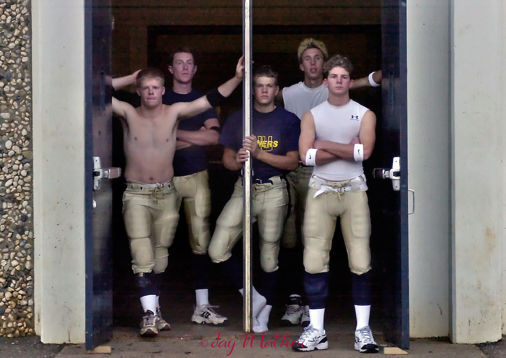 Nevada Union high school football players stand at their locker room door while the junior varsity game is played.  They were preparing themselves for the biggest game of their season against Grant High School