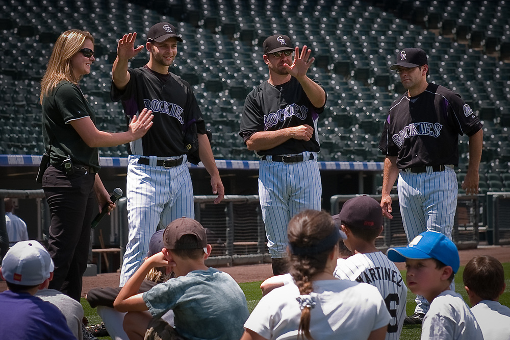 TAYLOR BUCHHOLZ, MIKE BARD and JOSE MORENO (left to right in uniform) of the Colorado Rockies congratulate the youngsters on a job well done.