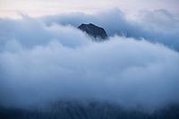Olstind mountain peak emerges from sea fog as viewed from Reinebrinen, Moskenesøy, Lofoten Islands, Norway