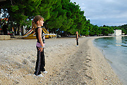 Two children (5 years old, 9 years old) standing on beach in late afternoon sun. Makarska, Croatia