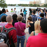 """People gather in Lake Eola park during the """"National Moment of Silence"""" event at the Lake Eola bandshell in downtown Orlando, Florida on Thursday, August 14, 2014. In light of the recent killing of eighteen year old Mike Brown in Ferguson, Missouri, citizens across America are gathering in solidarity to hold vigils and observe a moment of silence to honor victims of suspected police brutality. (AP Photo/Alex Menendez)"""