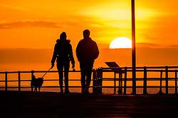 ©Licensed to London News Pictures.<br /> Aberystwyth UK,  25/03/2019. <br /> The spectacular sunset silhouettes a couple walking  on the seafront in Aberystwyth at the end of a lovely spring day of clear unbroken blue skies, as high pressure dominates the weather over much of the UK for the coming days<br /> photo Keith Morris/LNP